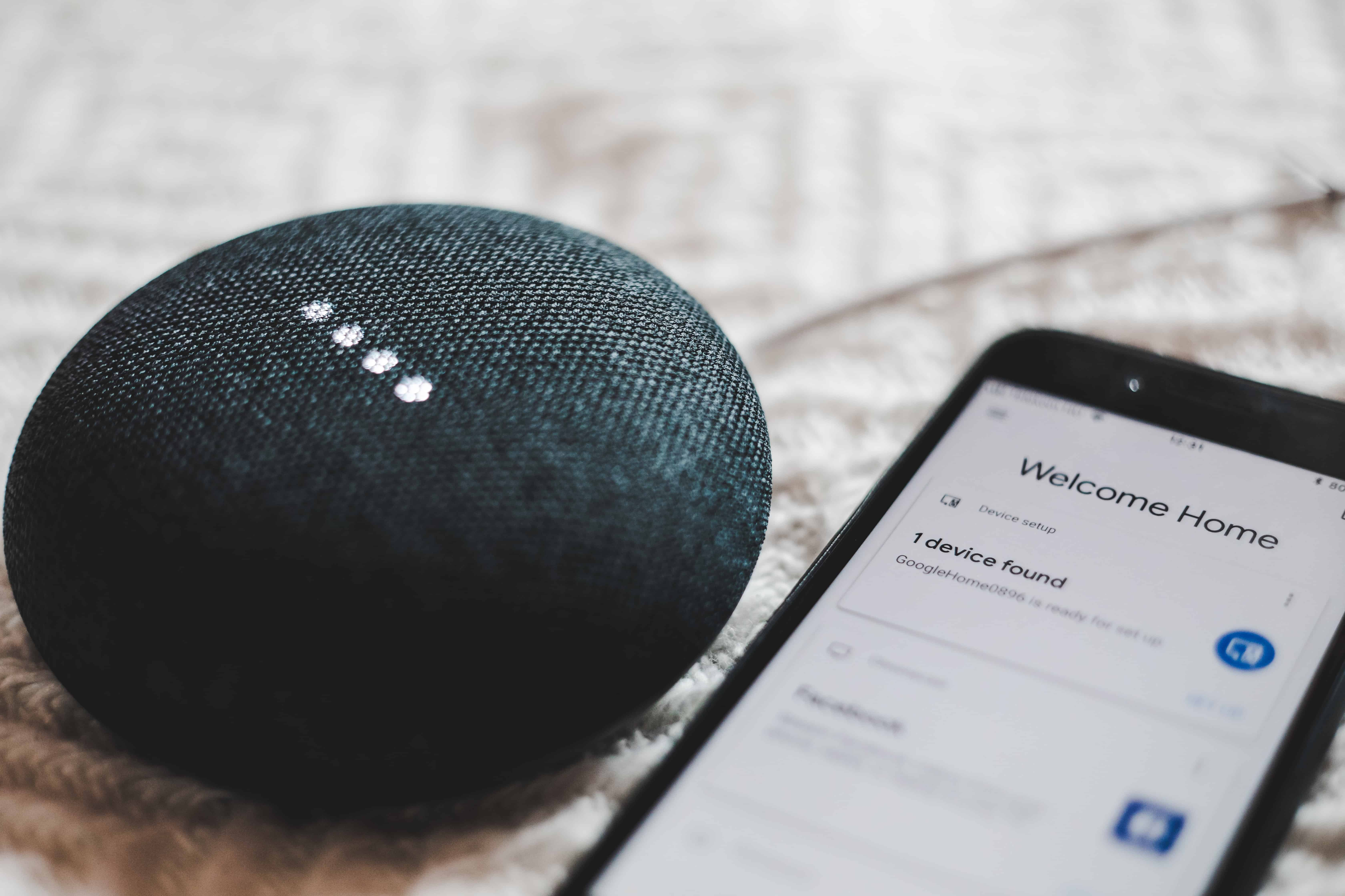 google home device beside smartphone